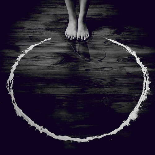 bare feet standing at the edge of a white circle on the ground